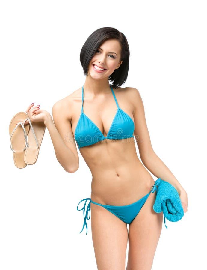 妇女佩带的比基尼泳装和保持毛巾和皮带 免版税库存图片
