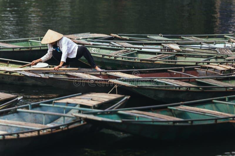 妇女佩带的白色衬衣,圆锥形帽子运载桨,在小船的攀登有许多小船的停止在河在的Trang洞穴 免版税库存照片
