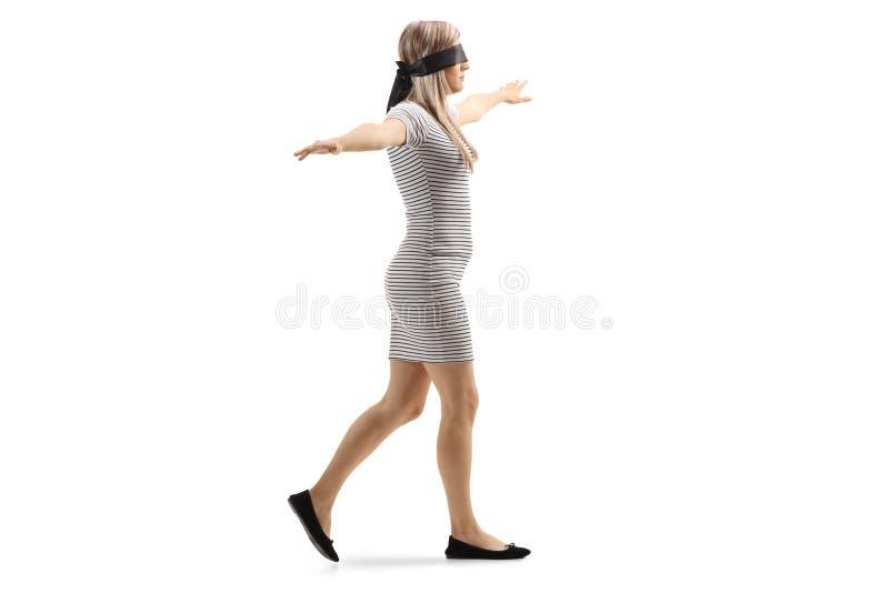 妇女佩带的眼罩和走与被涂的胳膊 库存照片