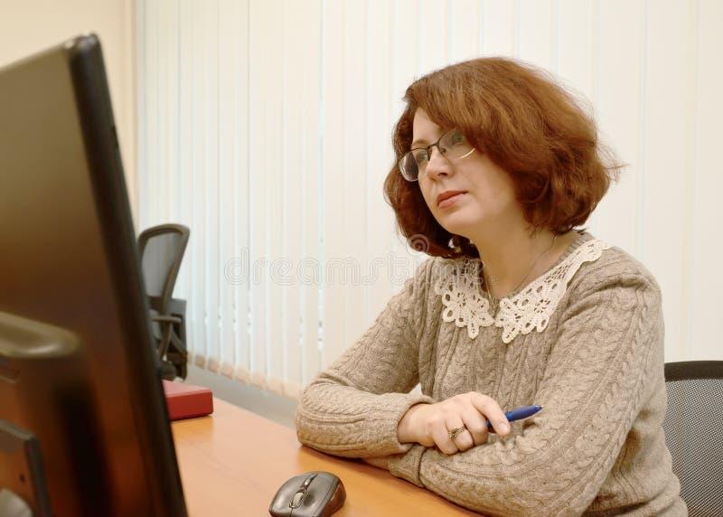 妇女佩带的眼镜殷勤地在计算机显示器看 免版税库存图片