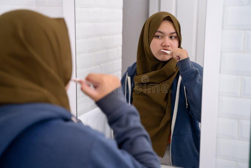 妇女佩带的hijab刷她的牙 免版税库存照片