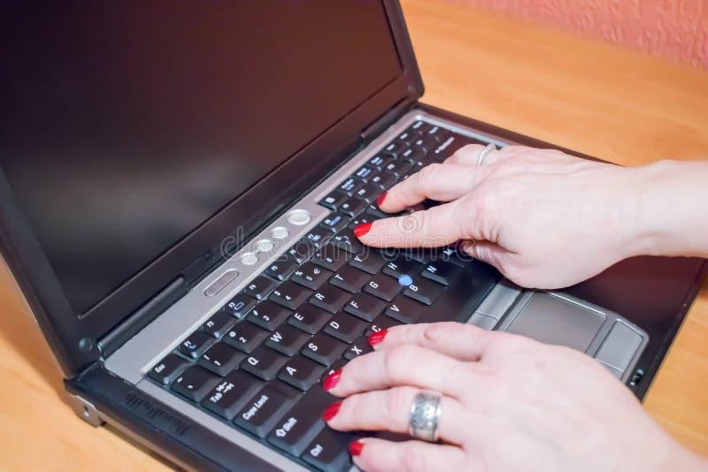 妇女佩带的smartwatch的手在她的便携式计算机键盘的  女性研究在咖啡馆的膝上型计算机 库存图片