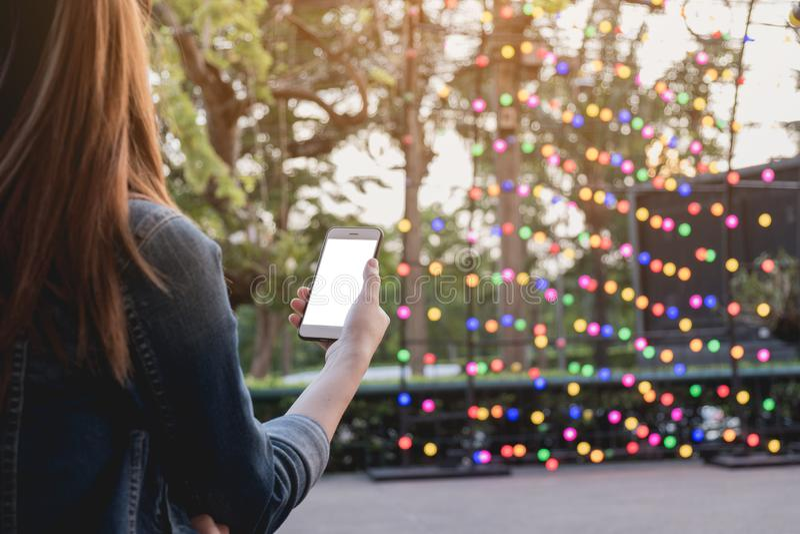 妇女使用了在公园的智能手机,假装在屏幕上 库存图片