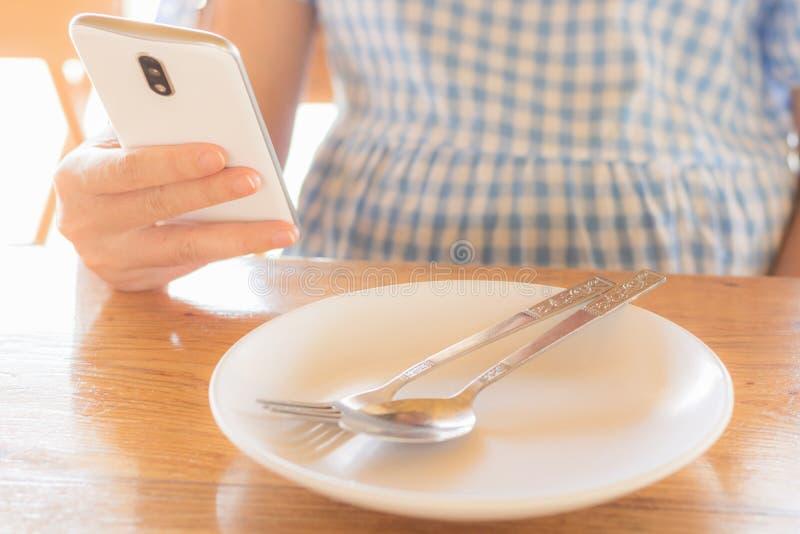妇女使用智能手机,当等待食物被服务i时 库存图片