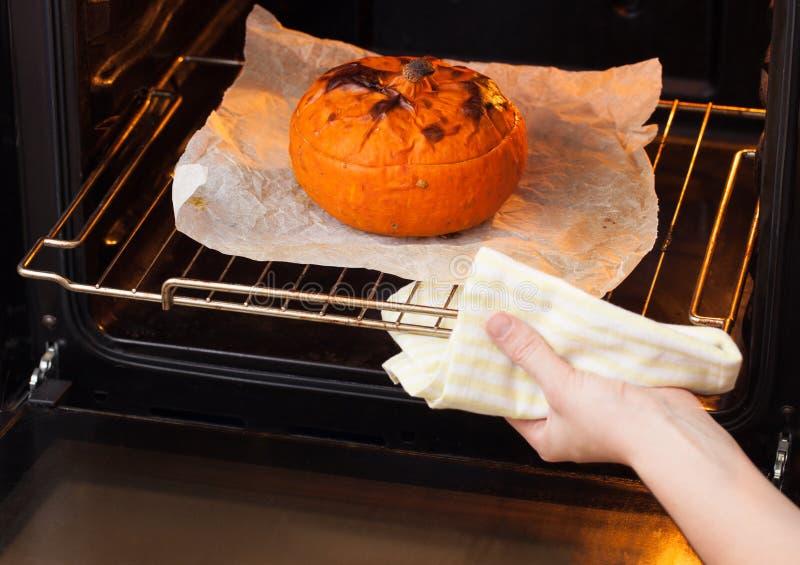 妇女使被烘烤的南瓜脱离烤箱 库存照片