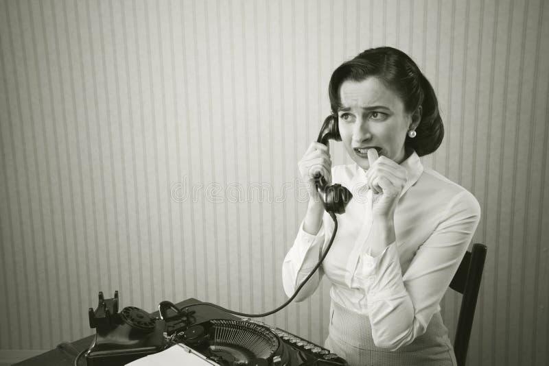 妇女谈话在电话在书桌 免版税库存照片