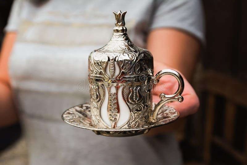 妇女供食在一个传统银色杯子的土耳其咖啡 库存图片