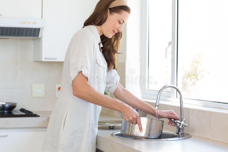 妇女侧视图有船的在水盆在厨房里 免版税库存图片