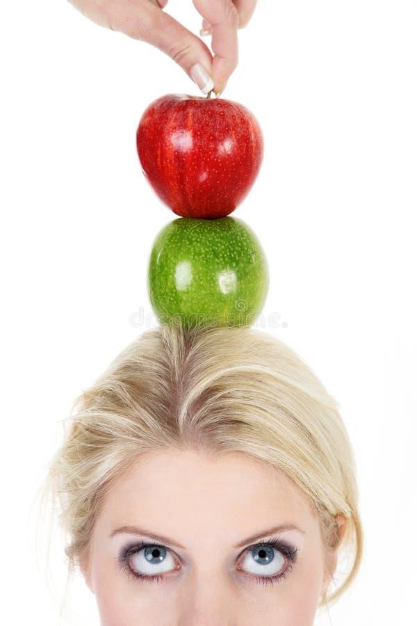 妇女保持平衡用苹果 免版税库存图片