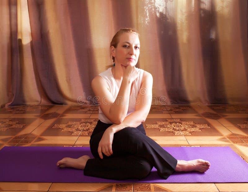 妇女信奉瑜伽者坐地板 库存图片