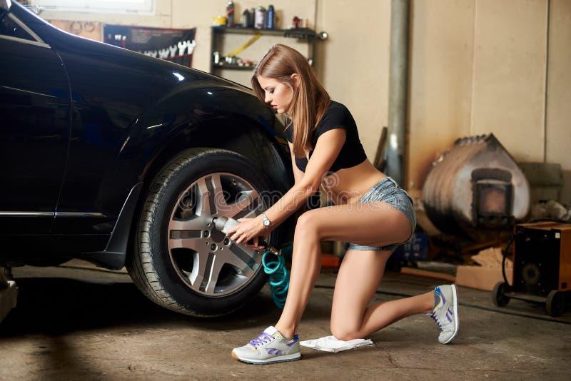 妇女修理一辆黑汽车的螺栓有一把自动螺丝刀的 库存照片