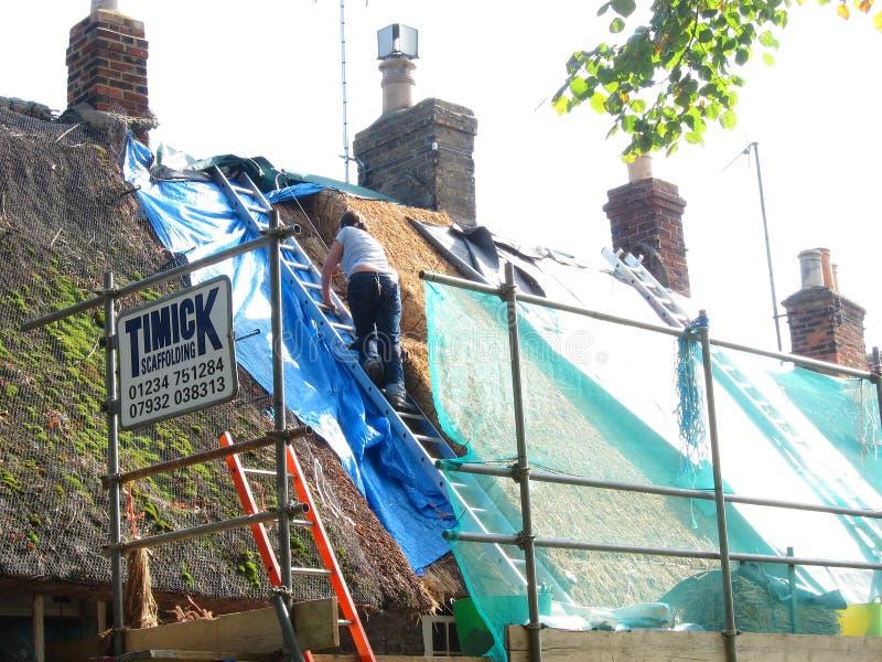 妇女修理屋顶的撒切尔。 免版税库存照片
