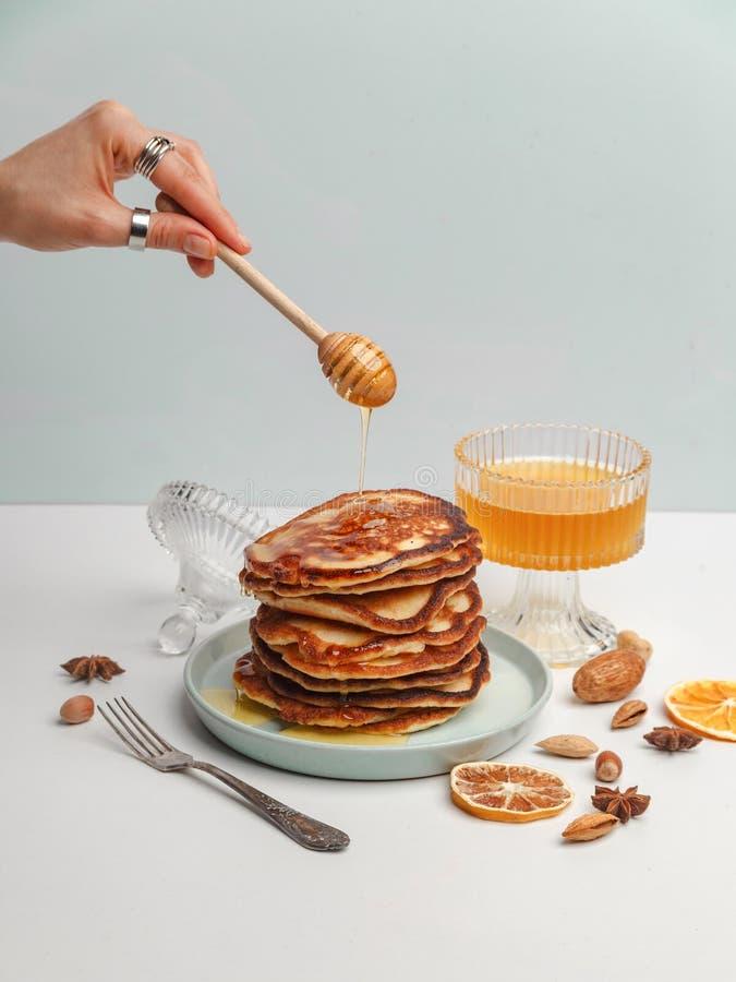 妇女倾倒在薄煎饼之上的蜂蜜 一顿可口早餐的概念 免版税库存图片