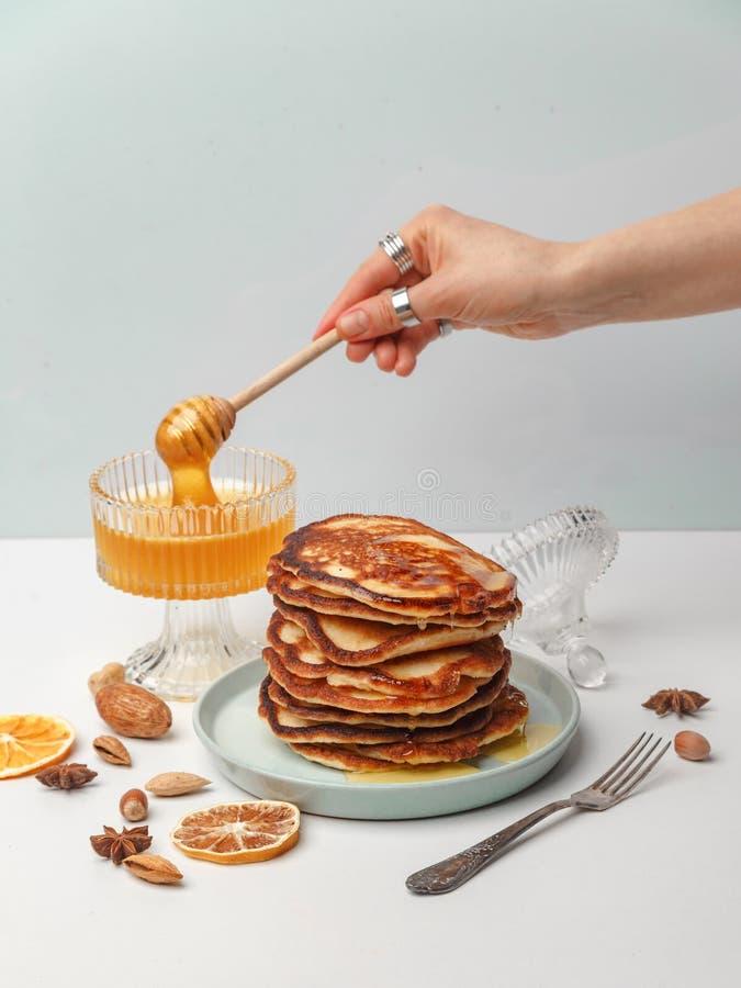 妇女倾倒在薄煎饼之上的蜂蜜 一顿可口早餐的概念 免版税库存照片