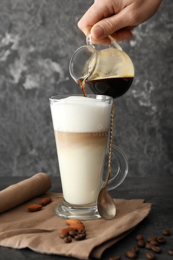 妇女倾吐的咖啡到玻璃杯子里用在灰色桌上的牛奶 库存图片