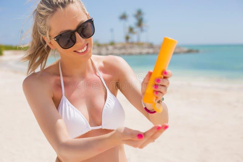 妇女倾吐的太阳保护奶油在手中 免版税库存图片