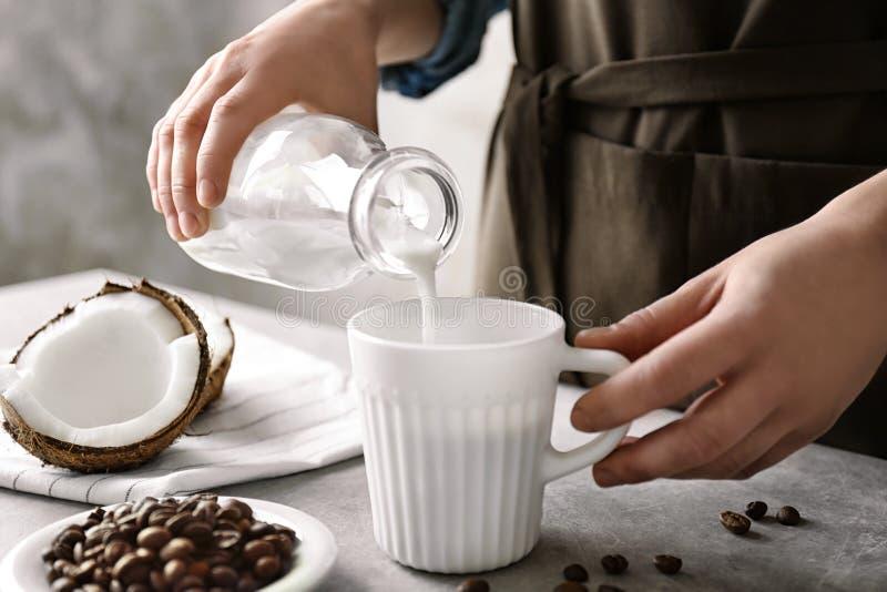 妇女倾吐的椰奶到咖啡里 图库摄影