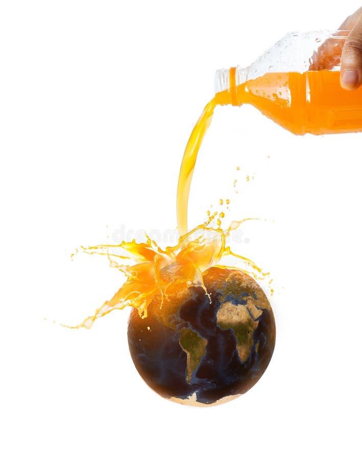 妇女倾吐的橙汁过去的手对新鲜的成熟橙色果子的与世界地图从美国航空航天局的图象来源 免版税库存照片
