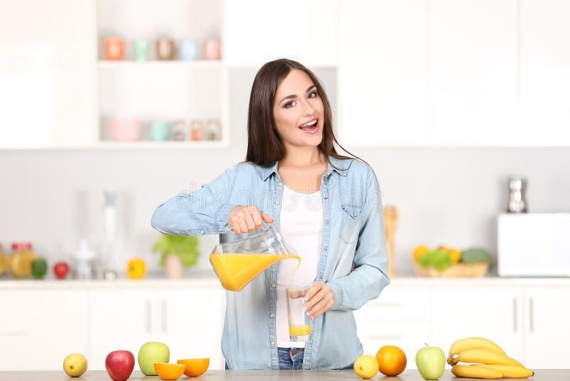 妇女倾吐的橙汁过去 免版税图库摄影