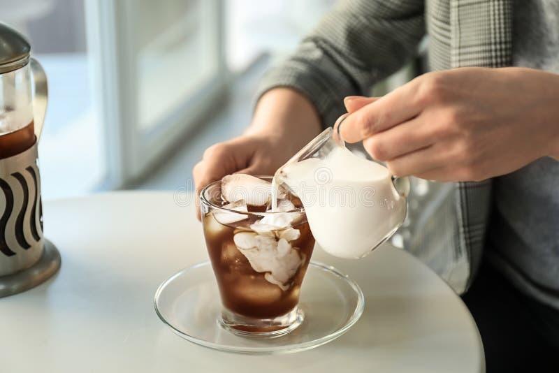 妇女倾吐的牛奶到玻璃杯子里用冷的咖啡在轻的桌上 免版税库存照片