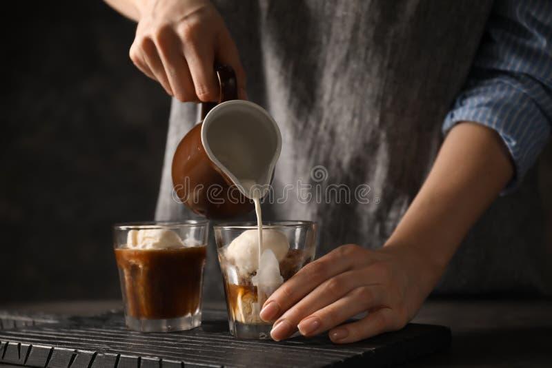 妇女倾吐的牛奶到玻璃里用咖啡和冰淇淋 免版税库存照片