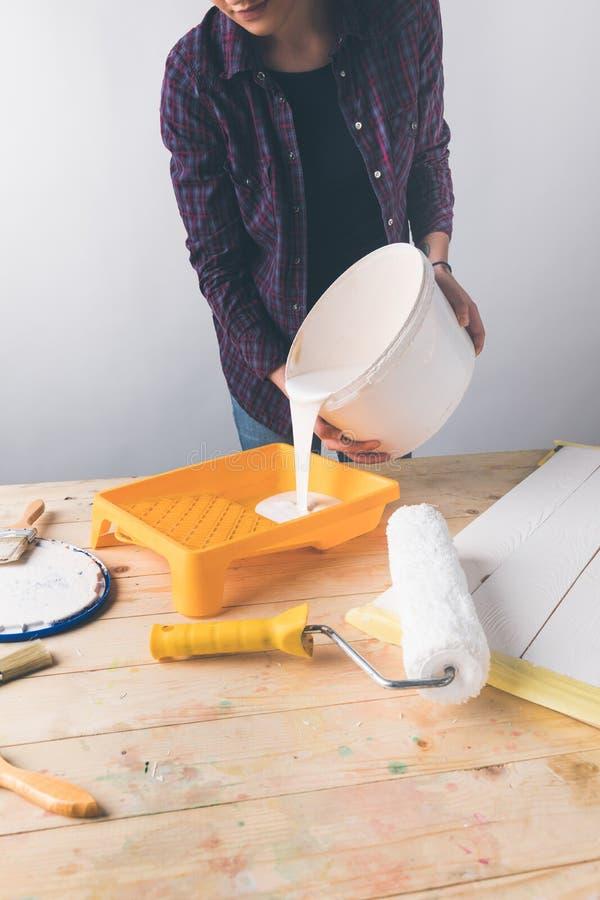 妇女倾吐的白色油漆到塑料盘子里 免版税库存照片