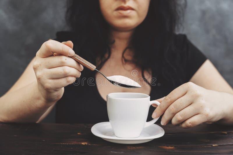 妇女倾吐的糖到咖啡杯里 免版税库存照片