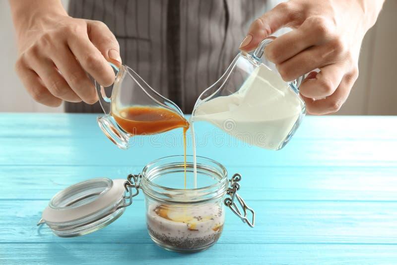 妇女倾吐的酸奶和焦糖调味入玻璃瓶子 免版税库存照片