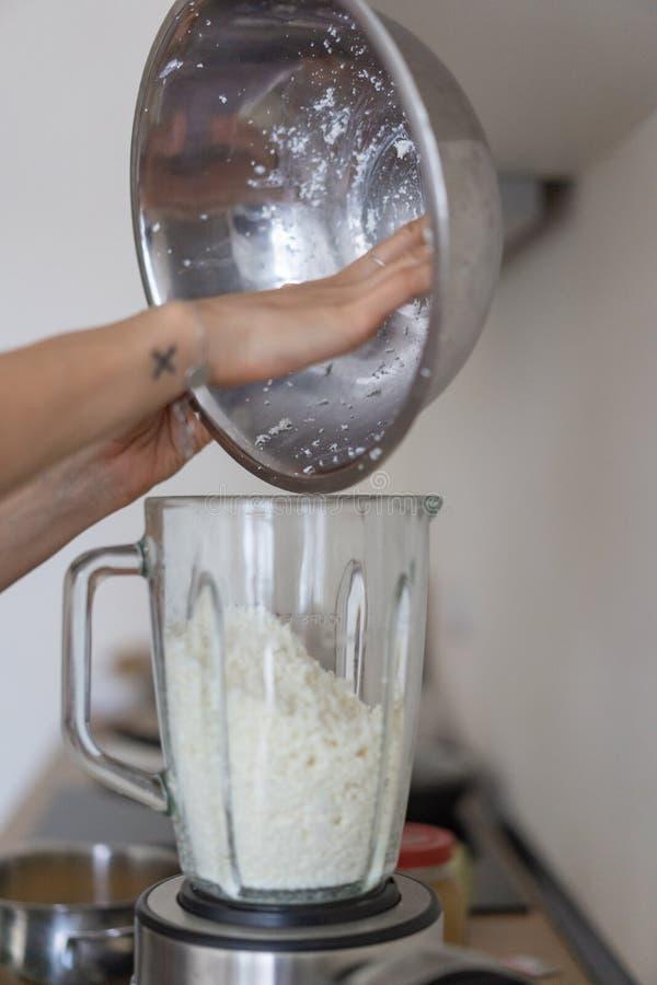 妇女倾吐的酸奶干酪到一台搅拌器里在厨房里 免版税库存图片