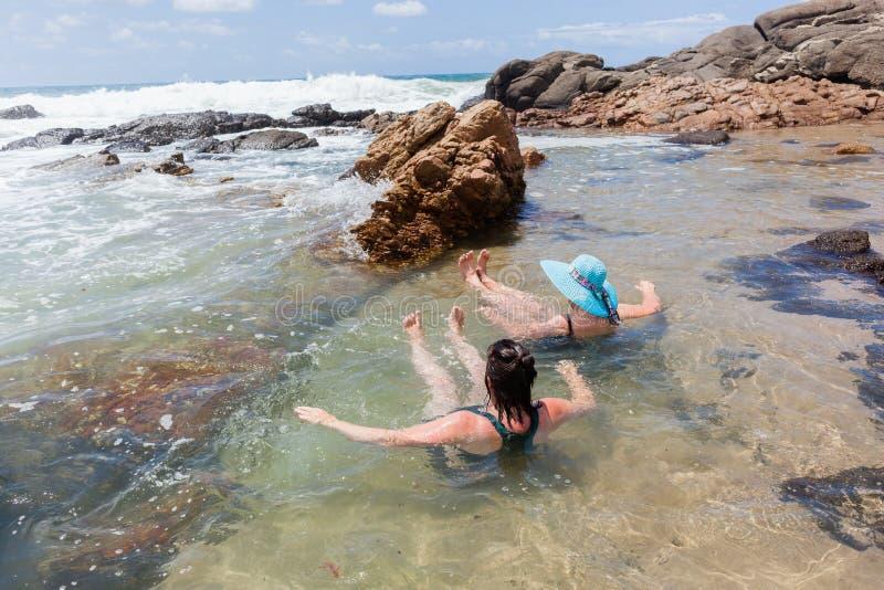 妇女假日海滩岩石水池 免版税库存照片