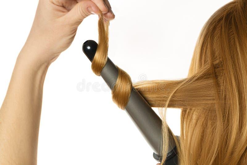 妇女做一根卷曲的头发由她自己 免版税库存图片