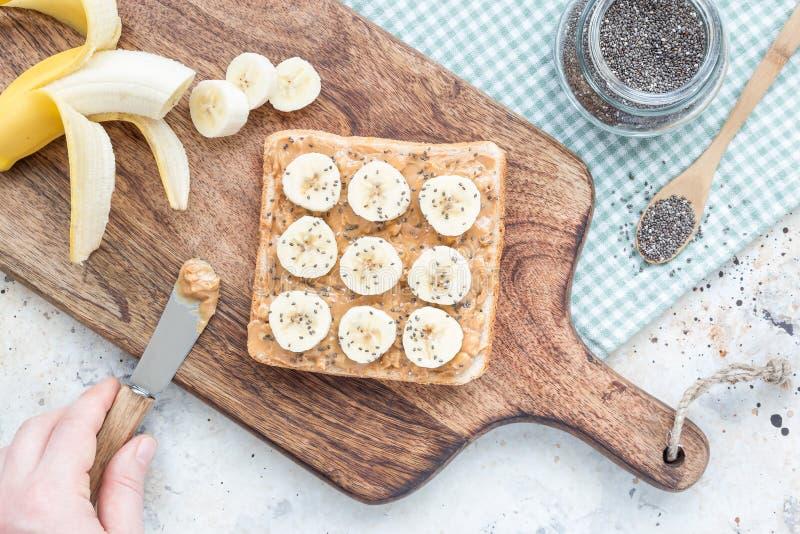 妇女做健康三明治用嘎吱咬嚼的花生酱,香蕉 库存照片
