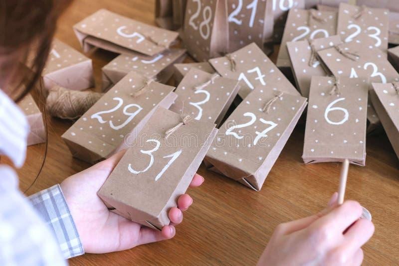 妇女做圣诞节孩子的出现日历 在袋子写一个数字由刷子和白色油漆 特写镜头手 免版税库存图片