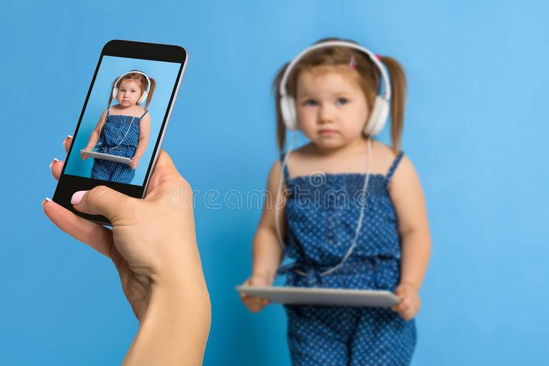 妇女做照片的` s手有一个手机的一个小女孩 在一个手机的选择聚焦有a画象的  库存图片