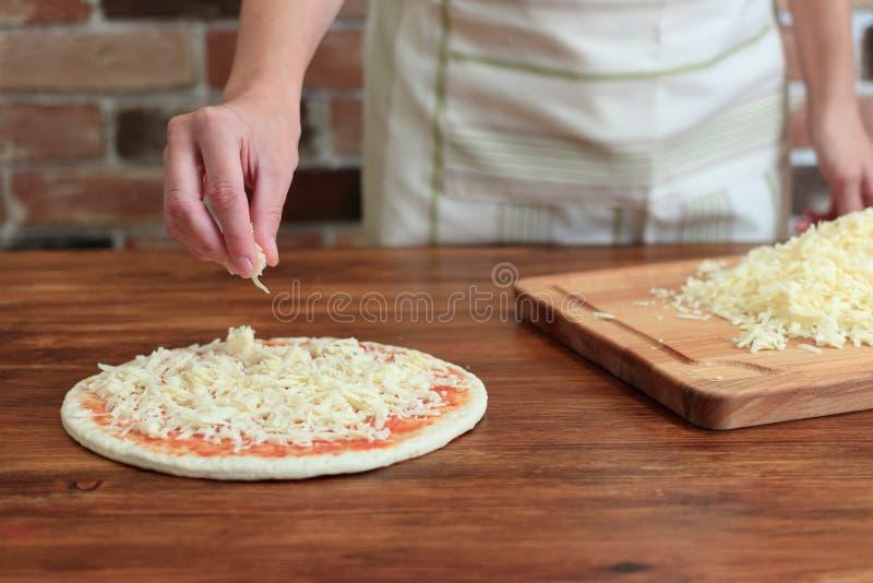 妇女做薄饼,洒在面团的乳酪 免版税库存图片