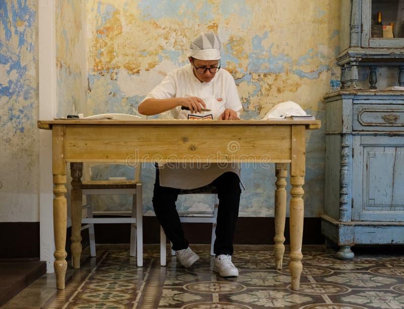 妇女做orecchiette,耳朵形状的面团,传统对意大利的普利亚地区 免版税图库摄影
