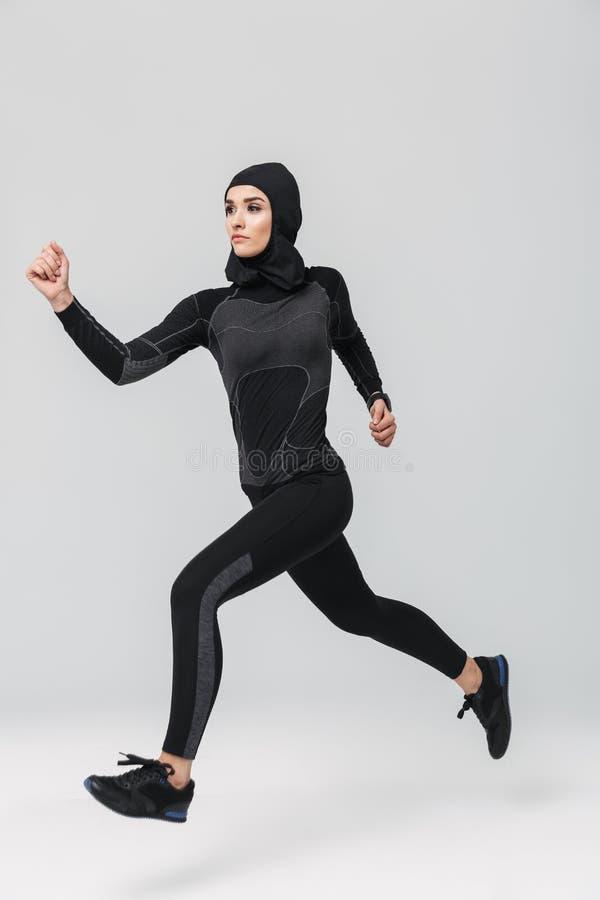 妇女健身回教做的锻炼被隔绝在白色墙壁背景 免版税图库摄影