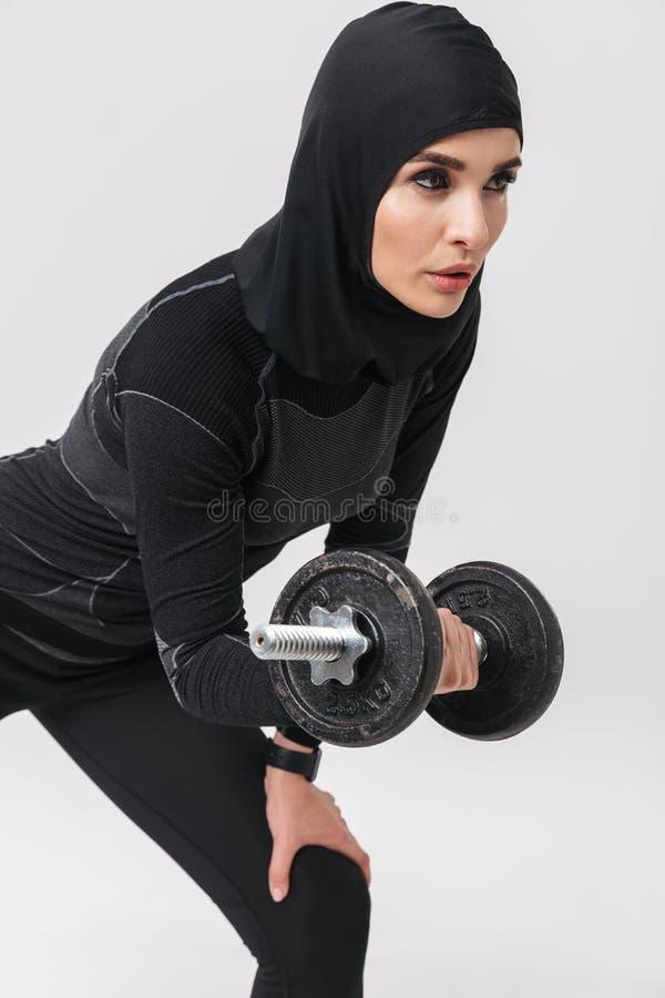 妇女健身穆斯林摆在被隔绝在白色墙壁背景做与哑铃的锻炼 免版税库存图片