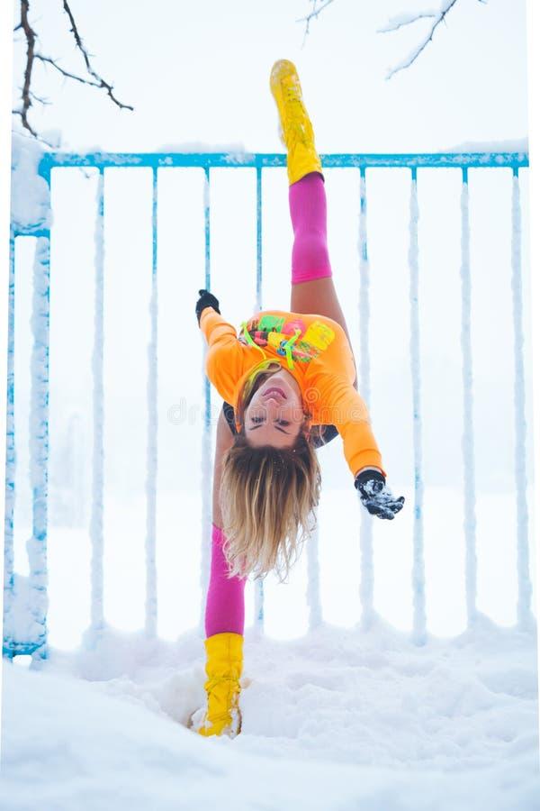 妇女健身辅导员锻炼室外在雪在金属篱芭冬天之前 图库摄影