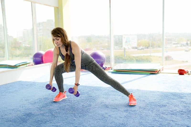 妇女健身 做在健身房的美丽的白种人资深妇女锻炼 r 免版税图库摄影