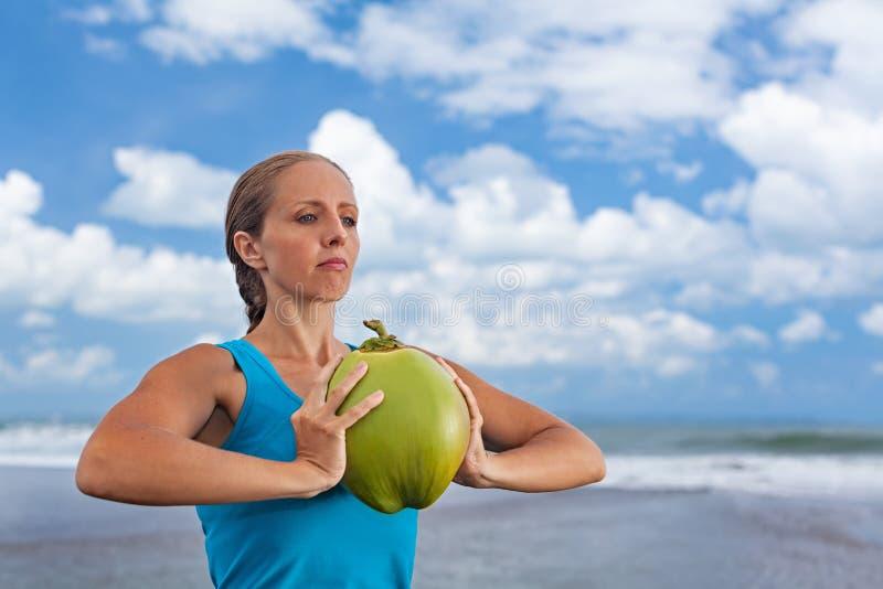 妇女健身锻炼用在海洋海滩的未加工的椰子 免版税库存照片