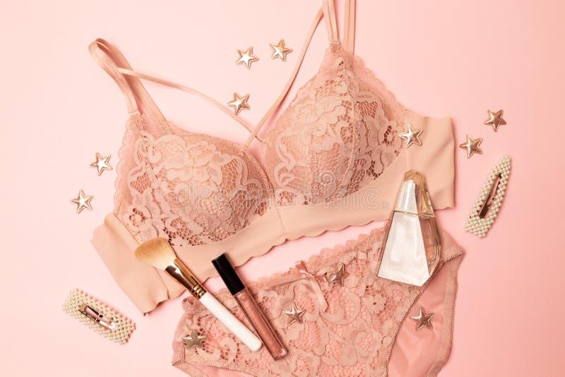妇女典雅的桃红色鞋带胸罩和内裤,首饰 时髦的女用贴身内衣裤平的位置 库存照片