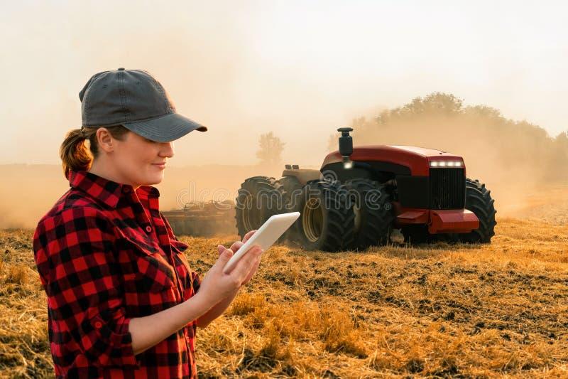 妇女农夫控制一台自治拖拉机 免版税库存照片
