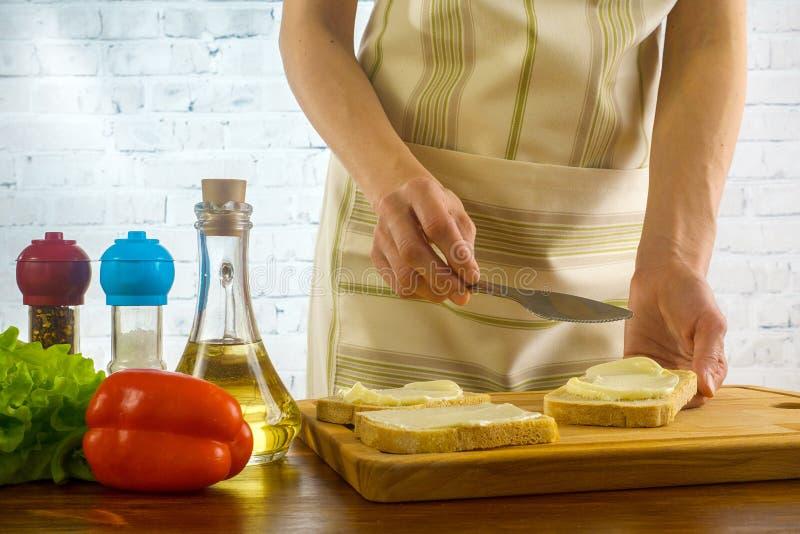 妇女准备三明治的和传播在面包涂黄油 图库摄影