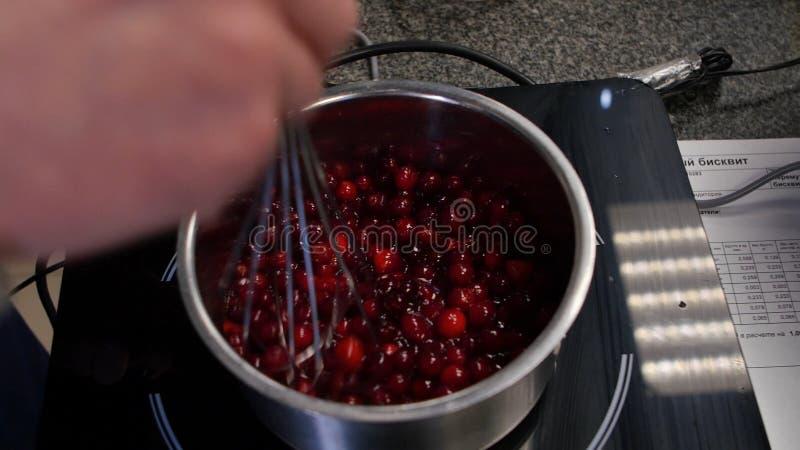 妇女准备红浆果的果酱,女性做盘,健康吃的和烹调概念的橘子果酱 免版税图库摄影