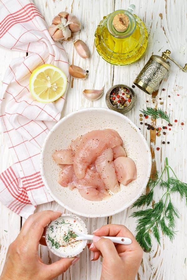 妇女准备鸡在希腊酸奶调味汁的内圆角矿块用柠檬、大蒜、莳萝和香料 r 库存照片