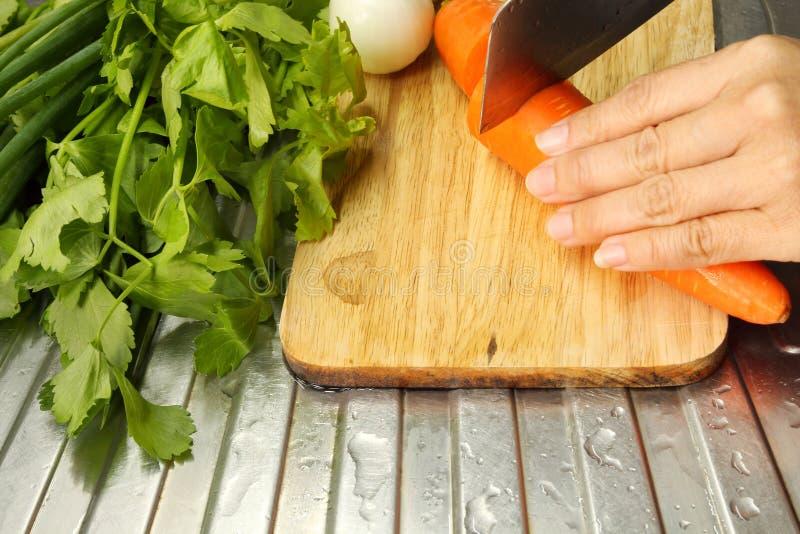 妇女切口红萝卜和菜的手在一个木板 免版税库存图片