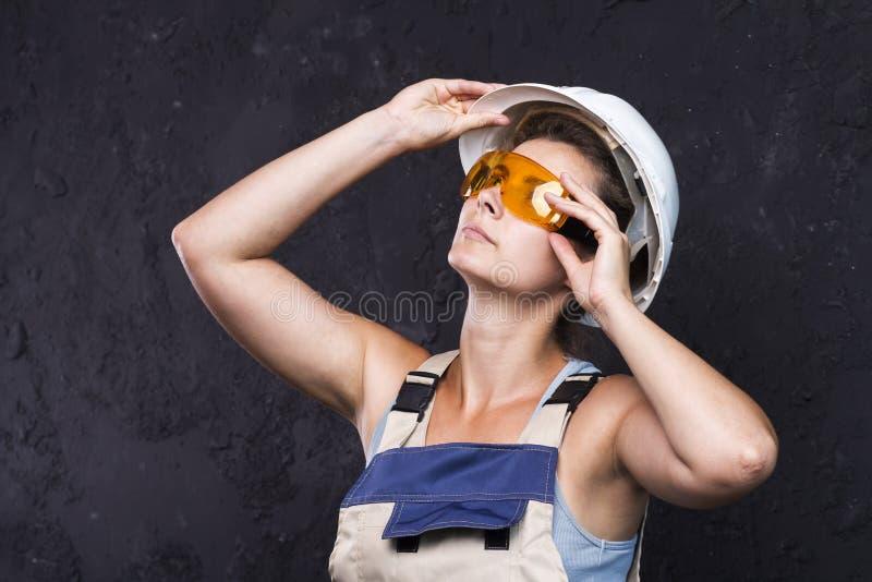 妇女制服有白色盔甲的和防护建筑玻璃的建造者工作者在黑背景 工作服的妇女 免版税库存图片