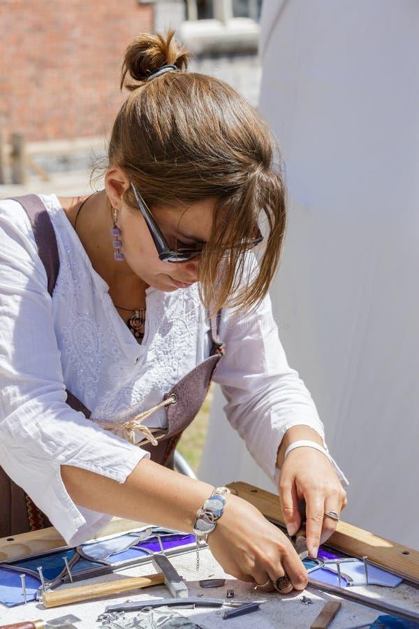妇女制造商与污点玻璃一起使用 免版税图库摄影