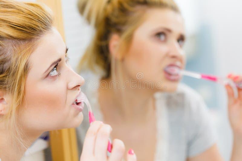 妇女刷子清理牙在卫生间里 库存照片